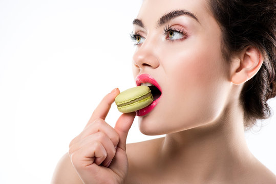 attractive woman eating green sweet macaron, isolated on white