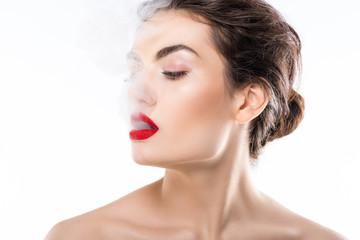 beautiful fashionable woman blowing smoke, isolated on white