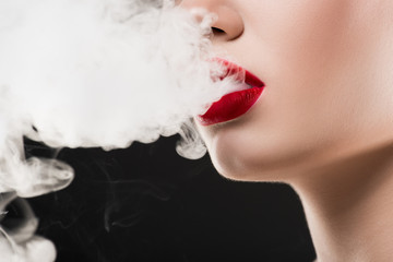 cropped view of smoking woman blowing smoke, isolated on grey
