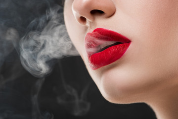 cropped view of girl with red lips blowing smoke, isolated on grey