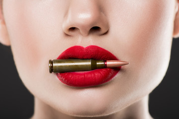 cropped view of woman holding bullet in red lips, isolated on grey Wall mural