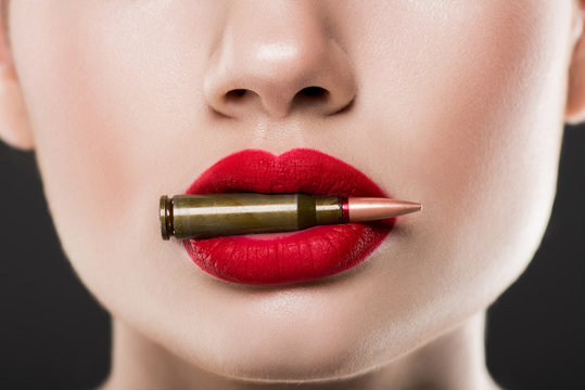 cropped view of woman holding bullet in red lips, isolated on grey