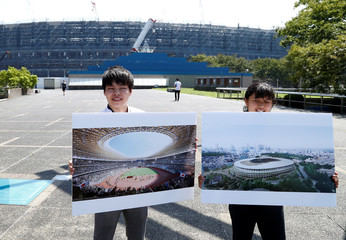 Media operations staff hold design pictures of the new National Stadium and sports complex for Tokyo 2020 Olympic games near the construction site in Kasumigaoka, Tokyo