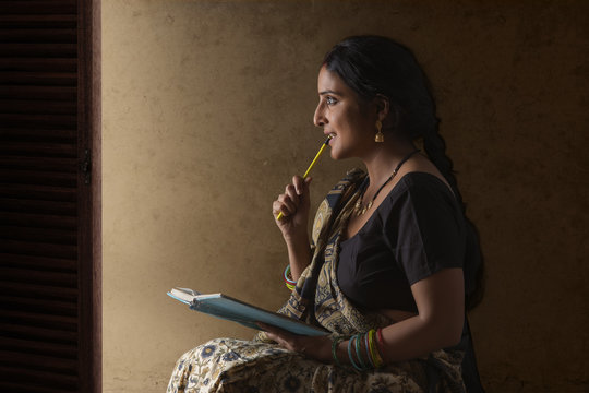 Woman wearing sari holding notebook and pencil