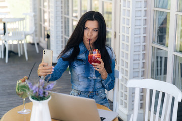 Front view of a bright brunette with long hair, has a European appearance, makes selfie on a smartphone, drinks her tasty cocktail through a straw, waits for her friends at a table in a cafe.