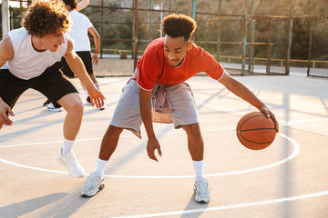 Portrait of athletic american and caucasian men playing basketball at the playground outdoor, during summer sunny day