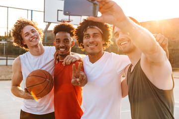 Young handsome men smiling and taking selfie on mobile phone, while playing basketball at playground outdoor during summer sunny day