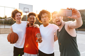 Portrait of cheerful sporty men smiling and taking selfie on smartphone, while playing basketball at playground outdoor during summer sunny day