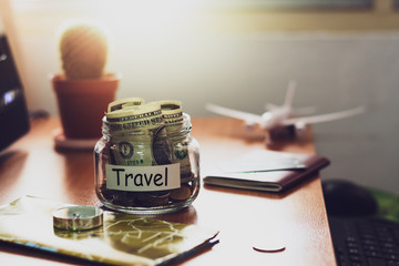 Travel budget concept. Money for travel savings in a glass jar on working desk.