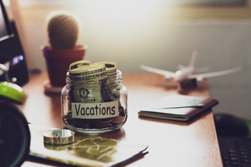 Vacation budget concept. Money for vacations savings in a glass jar on working desk.