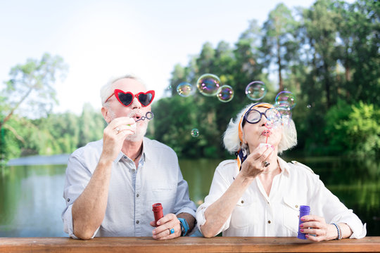 Grandfather and grandmother. Grandfather and grandmother feeling entertained while using soap bubbles of their grandchildren