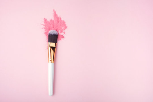 Makeup Brush on pink Background with Colorful Pigment Powder. Top view