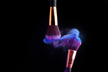 Make-up brush with colorful powder splashes explosion on black background