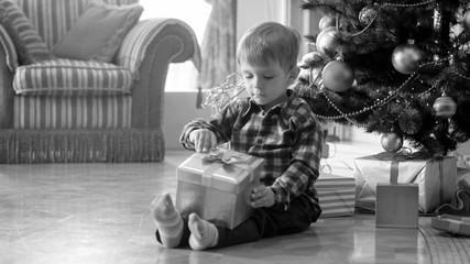 Black and white image of cute toddler boy sitting under Christmas tree and pulling bow on gift box