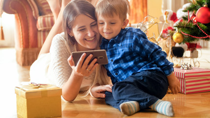 Portrait of cheerful smiling mother with baby lying on floor at living room and watching video on smart phone