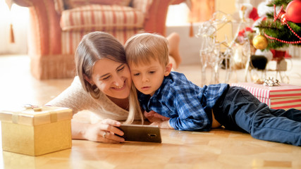 Portrait of smiling happy mother with toddler boy lying at living room under Christmas tree and watching video on smartphone