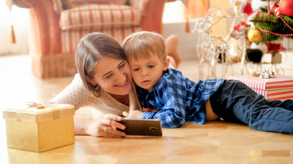 Portrait of little boy watching cartoons on mobile phone with mother under Christmas tree