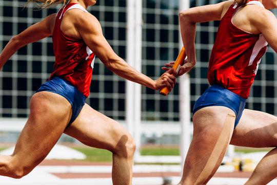 relay race passing of baton women team runners