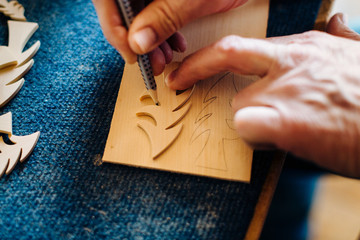 Carpenter drawing outline of wooden christmas tree, close up of hands