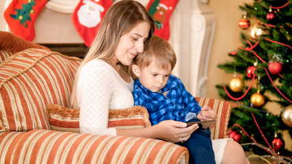 Beautiful young mother sitting in armchair with her little boy next to Christmas tree and watching video on smartphone