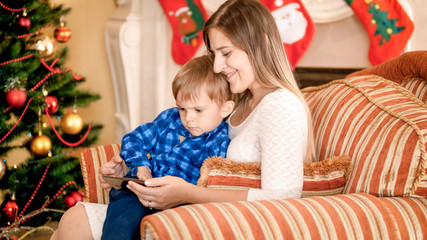Happy smiling mother with her baby watching video on smartphone in armchair next to Christmas tree