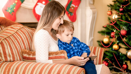 Little toddler boy sitting with mother next to Christmas tree and watching cartoons on mobile phone