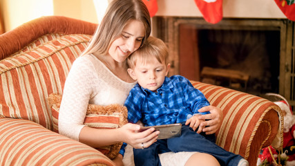 Smiling young mother with her son watching cartoons sitting in armchair at living room
