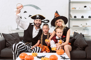 portrait of family in various halloween costumes at coffee table with pumpkins at home