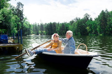 Summer day. Aged beaming wife and husband feeling relaxed while sitting in little boat on warm summer day