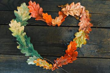 Oak leaves heart frame on wooden desk. Autumn background concept. Fall, planks, raining, September, October, November, thanksgiving, top view