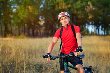 Smiling cyclist against autumn forest