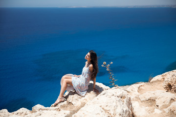 Brunette in a dress sits on the edge of the cliff overlooking the sea