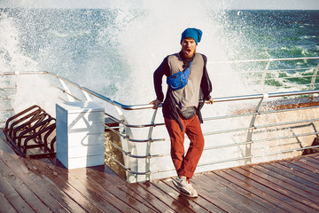 Hipster against railing, sea splash in background