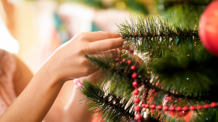 Closeup image of young girl hanging baubles on Christmas tree branches