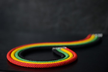 Beaded necklace in Jamaican style on a dark background close up