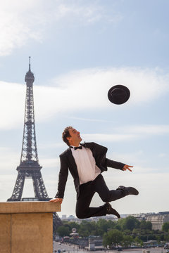 Formally Dressed Man Throws His Hat in the Air While Jumping, in Paris, with the Eiffel Tower Behind Him