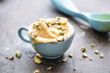 Homemade saffron ice cream with pistachio nuts, melting