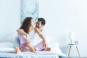 happy young couple in pajamas sitting on bed and smiling each other