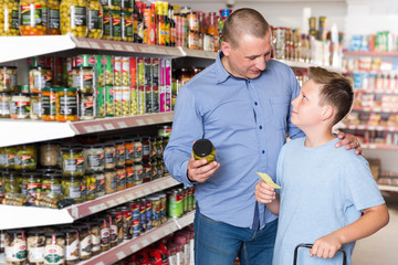 Portrait  of father and boy choosing food with shopping list