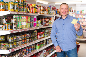 man buying food products on shopping list