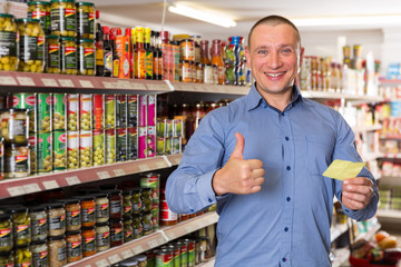 male with shopping list in products store