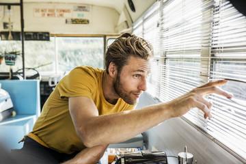Man in an old bus peeking through sunblind