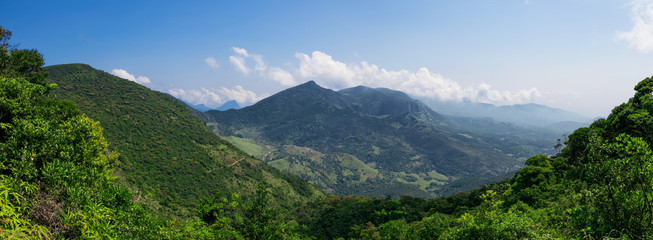 Panoramic view of a mountain with blue sky and clouds on background in Sri Lanka.