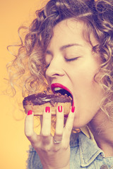 beautiful girl biting a chocolate-coated donut