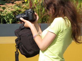 Young woman with a SLR camera in her hands. Girl photographing in sunny day