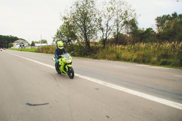 Green sport motorbike with racer on the background of gray asphalt. Ukraine, Lviv.