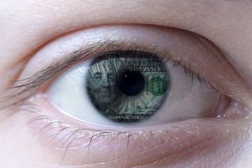 Human eye with a one hundred dollar bill with Benjamin Franklin portrait reflection