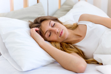 Young beautiful woman sleeping in her bed and relaxing