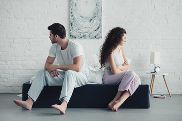 upset young couple in pajamas sitting with crossed arms on bed, relationship difficulties concept