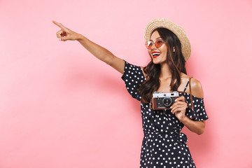 Happy brunette woman in straw hat and sunglasses posing